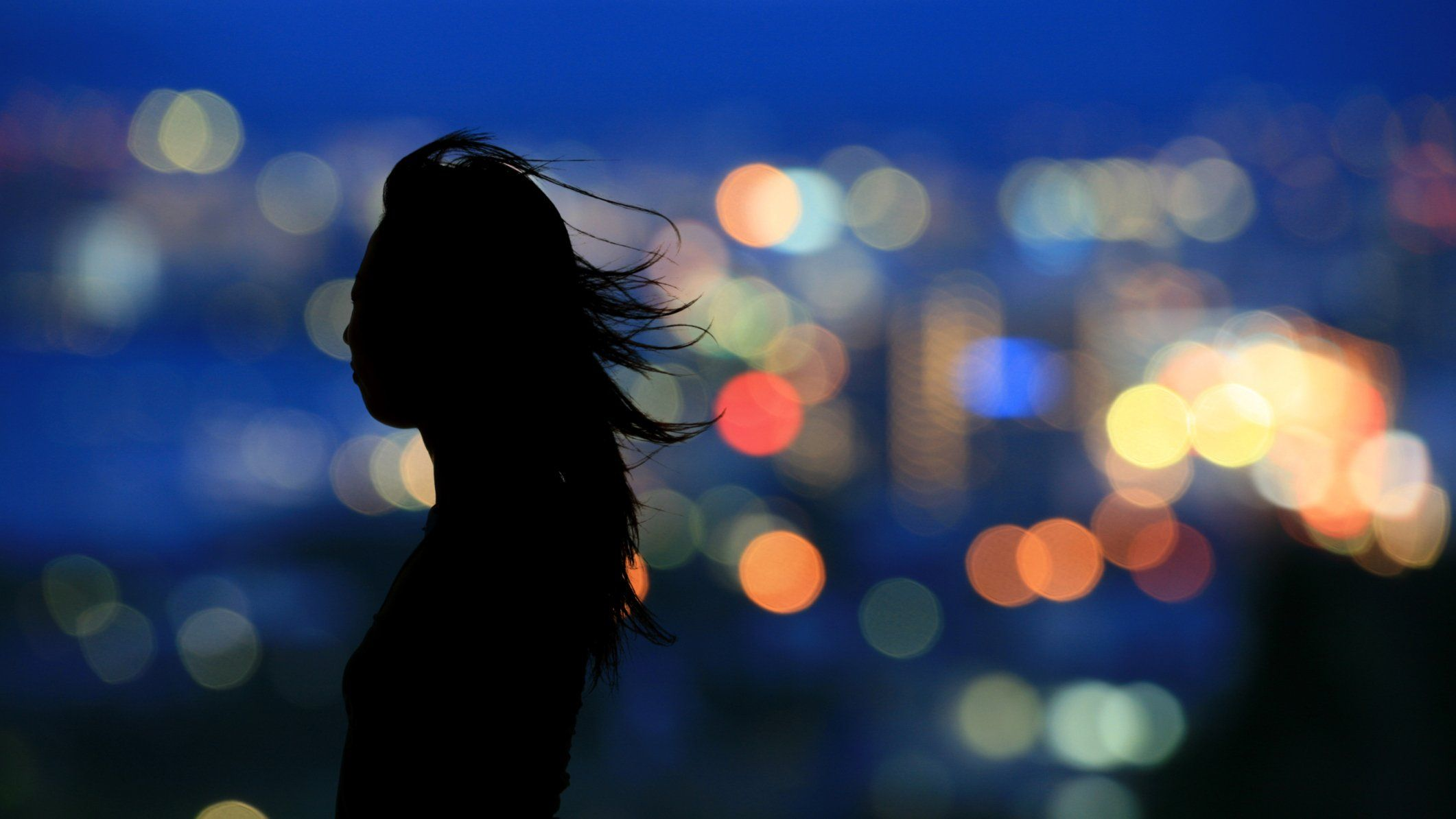 silhouette of woman in-front of city scape